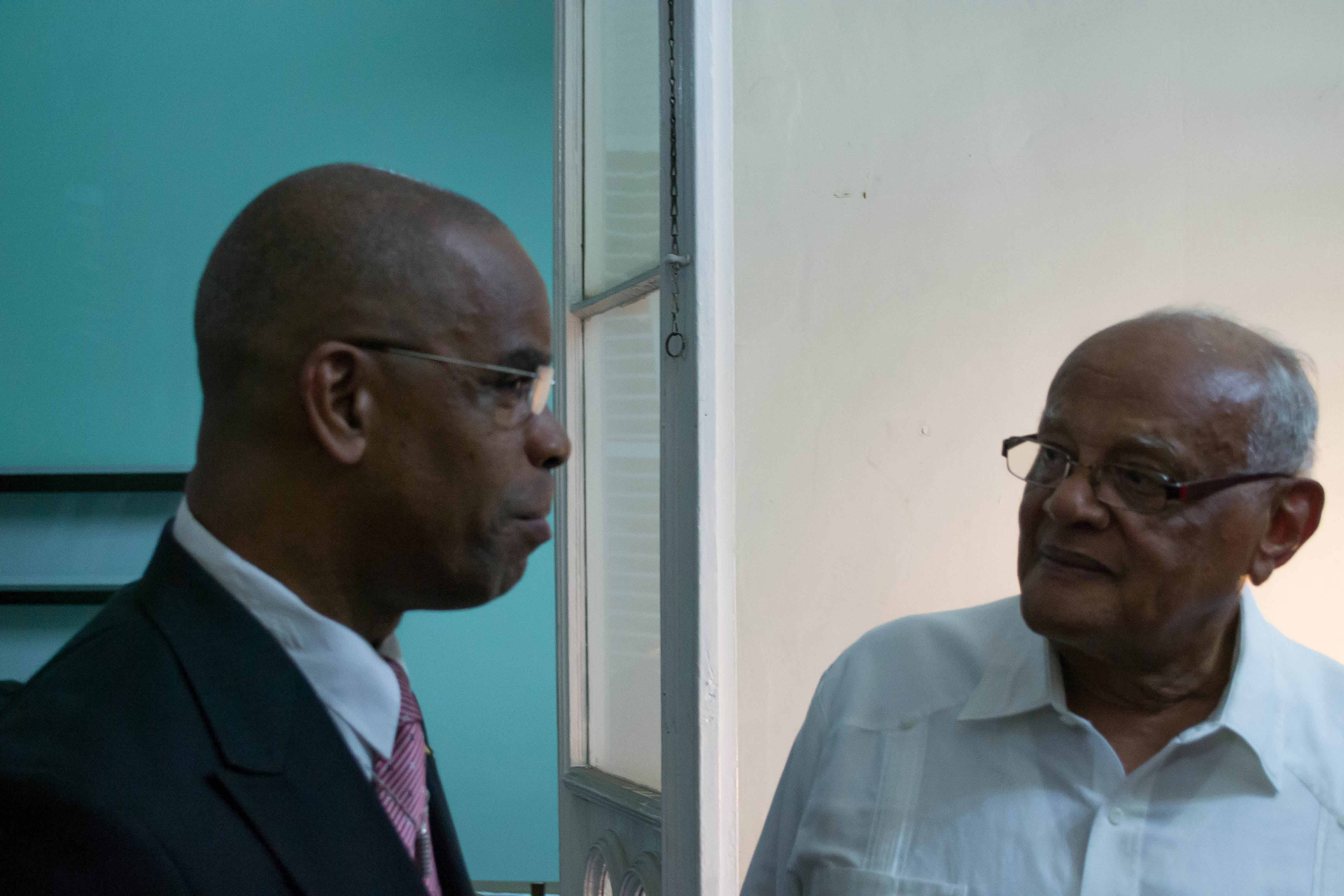 The Minister of National Diversity and Social Integration, the Honourable Rodger Samuel (left), and member of the Hayes Court Restoration Committee and the Honorary Consul of Barbados, Mr Audley Walker (right), in discussion.